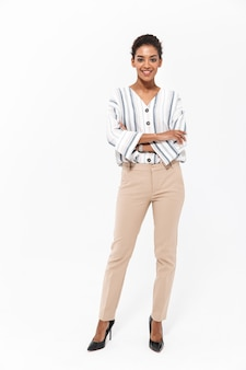 Full length portrait of a smiling young african businesswoman standing isolated over white wall
