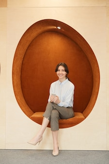 Full length portrait of smiling young businesswoman looking at camera while sitting in egg-shaped orange lounge zone of modern office or coworking space
