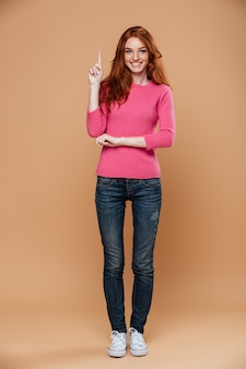 Full length portrait of a smiling young redhead girl pointing up with fingers