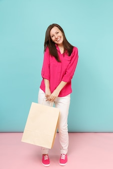 バラのシャツのブラウス、白いズボンのフルレングスの肖像画の笑顔の若い女性は、明るいピンクブルーのパステルカラーの壁に分離されたショッピングバッグを保持します。