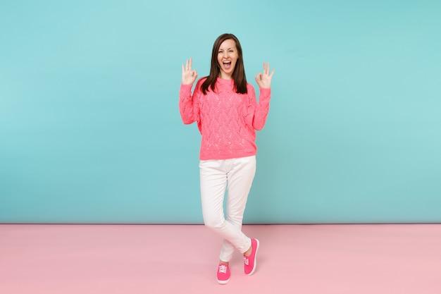 Ritratto a figura intera di giovane donna sorridente in maglione rosa lavorato a maglia, pantaloni bianchi in posa