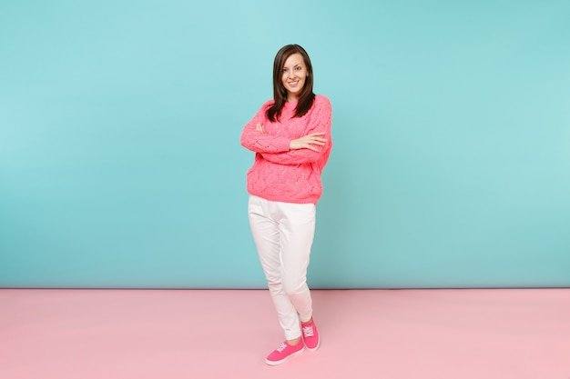 Full length portrait of smiling young woman in knitted rose sweater, white pants posing