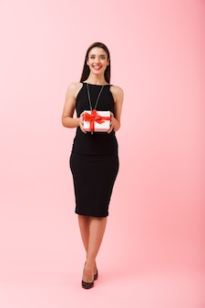 Full length portrait of a smiling young woman wearing black dress standing isolated over pink background, holding gift box