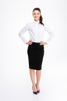 Full length portrait of smilling businesswoman standing with hands on hips isolated on a white wall