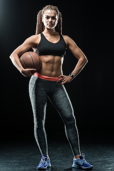 Full length portrait of a sports woman posing holding basketball isolated on a black background