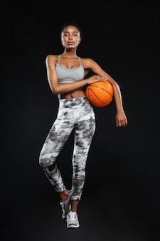 Full length portrait of a sports woman posing holding basketball isolated on a black wall