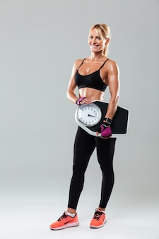 Full length portrait of a sportswoman standing and holding weights