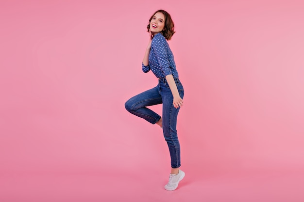 Full-length portrait of sporty girl with wavy hair. indoor shot of jumping young woman in jeans and blue shirt.