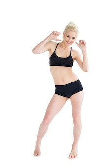 Full length portrait of a sporty young woman dancing