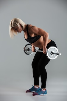 Full length portrait of a strong muscular adult sportswoman