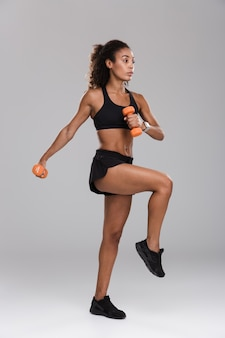 Full length portrait of a strong young african sportswoman doing exercises with dumbbells isolated over grey background