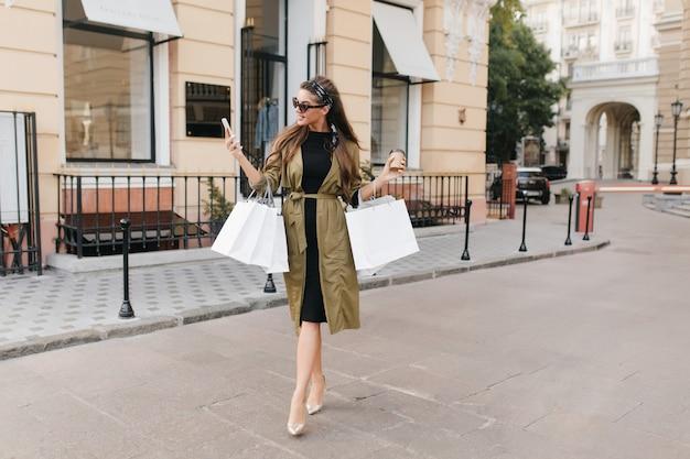 Ritratto a figura intera della splendida modella femminile che parla al telefono mentre trasporta borse per strada
