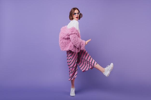 Ritratto a figura intera della splendida modella femminile indossa scarpe da ginnastica bianche alla moda e giacca di pelliccia. ragazza caucasica con capelli mossi che ballano sul muro viola.