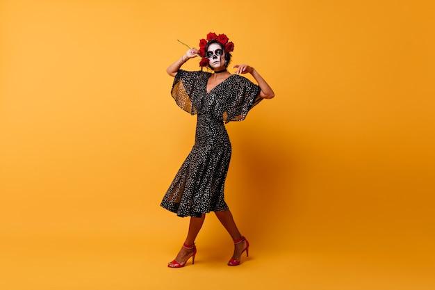 Ritratto a figura intera di stupefacente zombie femmina in abito messicano. ragazza magra ispirata in costume di halloween che balla sulla parete arancione.