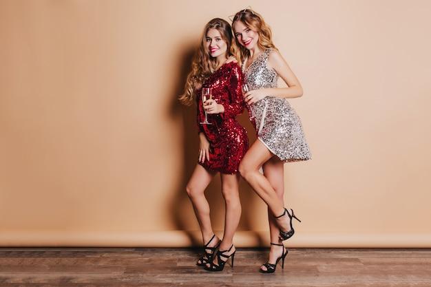 Ritratto a figura intera di splendide donne in abito di lusso che ballano insieme alla festa di capodanno