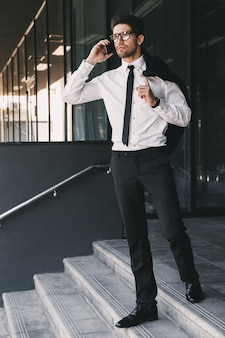 Full length portrait of stylish businessman dressed in formal suit standing outside glass building with jacket over his shoulder, and talking on mobile phone