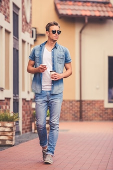 Full length portrait of stylish guy in jeans clothes.