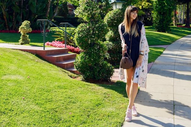 Ritratto integrale della donna sorridente alla moda che cammina sulla strada esotica vicino all'hotel in una giornata calda e soleggiata. trascorre le sue vacanze a los angeles.