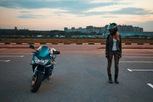 Full length portrait of stylish young caucasian female wearing khaki jeans, black leather jacket and protective helmet standing at parking lot and looking at blue motorbike parked next to her