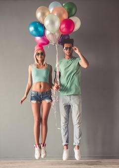Full length portrait of stylish young couple in sun glasses.