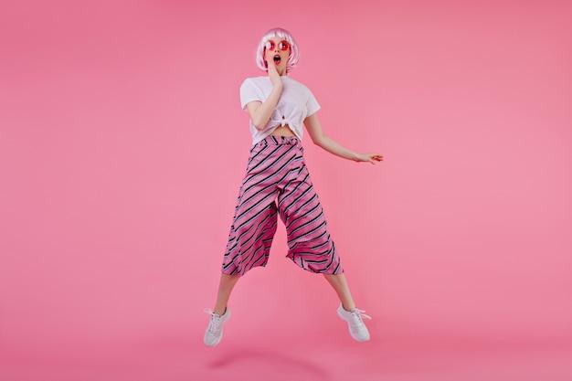 Ritratto integrale della ragazza felice sorpresa in peruke che salta sulla parete luminosa. bello modello femminile europeo che si diverte durante il servizio fotografico a periwig