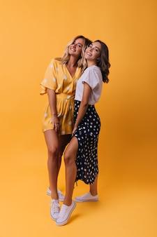 Ritratto a figura intera di ragazze abbronzate in abbigliamento casual. amici femminili accattivanti in piedi sull'arancia.