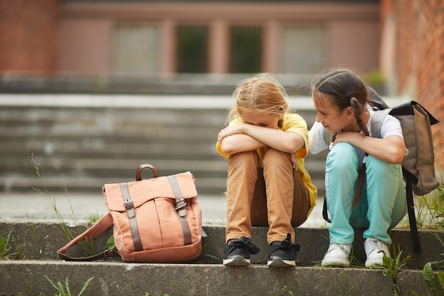 Full length portrait of teenage schoolgirl crying while sitting on stairs outdoors with smiling friend comforting her, copy space