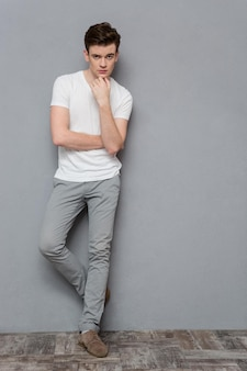 Full length portrait of thoughtful handsome young guy in white t-shirt and gray pants standing on gray wall