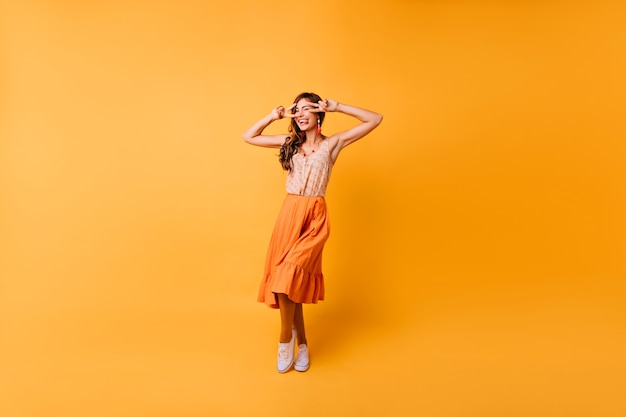 Full-length portrait of trendy emotional girl dancing on bright. jocund lady in long orange skirt expressing happiness.