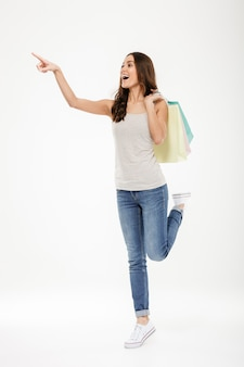 Full-length portrait of trendy woman pointing finger away and holding many shopping bags, isolated over white wall