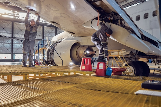Full length portrait of two engineer workers in uniform fixing and checking commercial airplane in hangar