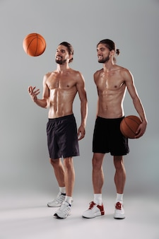 Full length portrait of a two muscular shirtless twin brothers