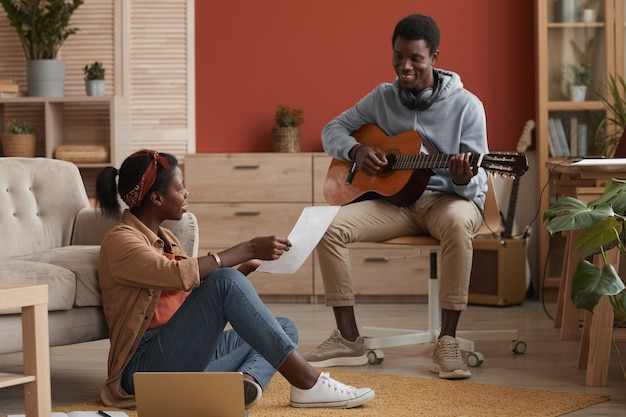 Full length portrait of two young african-american musicians playing guitar and writing music together in home recording studio