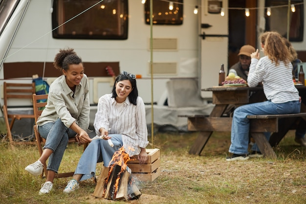 Full length portrait of two young women relaxing by fire outdoors while camping with van in forest c...