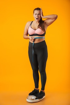 Full length portrait of an upset overweight young woman wearing sport clothing standing on scales isolated over yellow wall, holding measuring tape around her waist