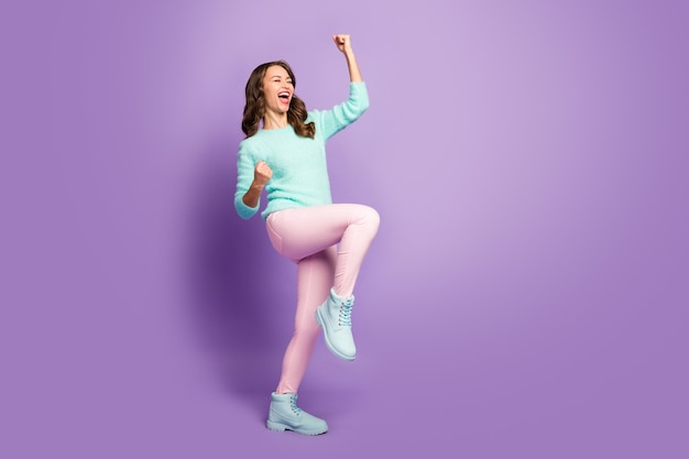 Full length portrait of wild delighted wavy lady celebrating football team winning sports competition wear fluffy pastel pullover pink pants boots.