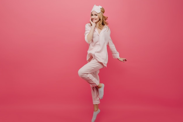 Full-length portrait of winsome girl in pajamas and socks dancing on pink wall. graceful caucasian female lady in eyemask having fun in morning.