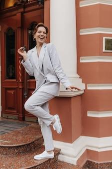 Ritratto integrale della donna in vestito grigio e scarpe da ginnastica bianche. elegante bella ragazza in giacca oversize e pantaloni sorrisi e pose all'esterno