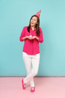 バラのシャツのブラウス、白いズボン、明るいピンクブルーのパステルカラーの壁に分離されたカップケーキのポーズで誕生日の帽子のフルレングスの肖像画の女性。