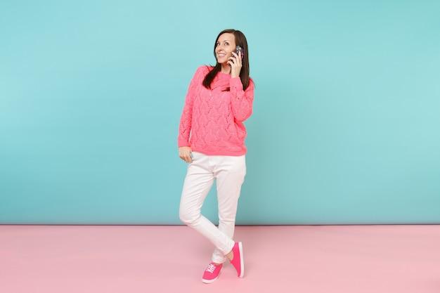 Ritratto a figura intera di donna in maglione rosa lavorato a maglia, pantaloni bianchi che parla al cellulare mobile