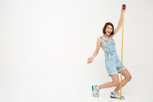Full length portrait of woman measure herself with tape