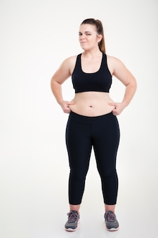 Full length portrait of a woman pinches fat on her belly isolated on a white wall