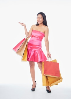 Full length portrait of woman in pink dress with shopping bags isolated on white background