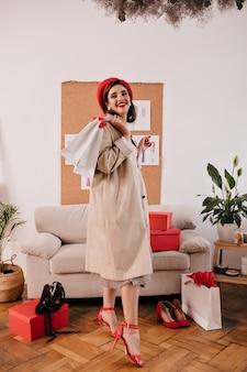 Ritratto integrale della donna in berretto rosso e cappotto beige. signora carina in abiti autunnali leggeri e cappello luminoso tiene gli acquisti in appartamento.