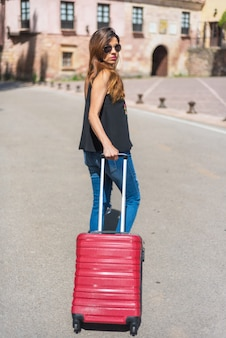 Full length portrait of a woman traveling with trolley. focus on trolley.