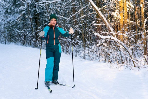 Full-length portrait of young active beautiful woman skiing in snowy winter forest
