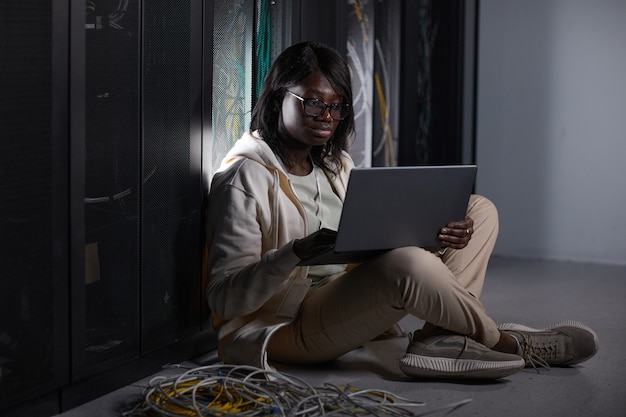 Full length portrait of young african-american woman using laptop in server room and sitting on floor while working with supercomputer at data center, copy space
