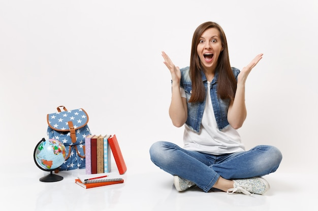 Full length portrait of young amazed woman student in denim clothes spreading hands sitting near globe backpack, school books isolated