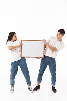 Full length portrait of a young angry attractive couple standing isolated over white wall, presenting blank board