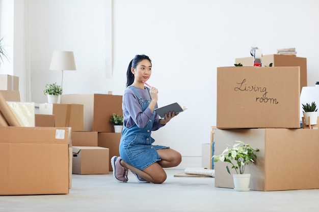 Full length portrait of young asian woman organizing moving in process while sitting on floor next to cardboard boxes and holding planner